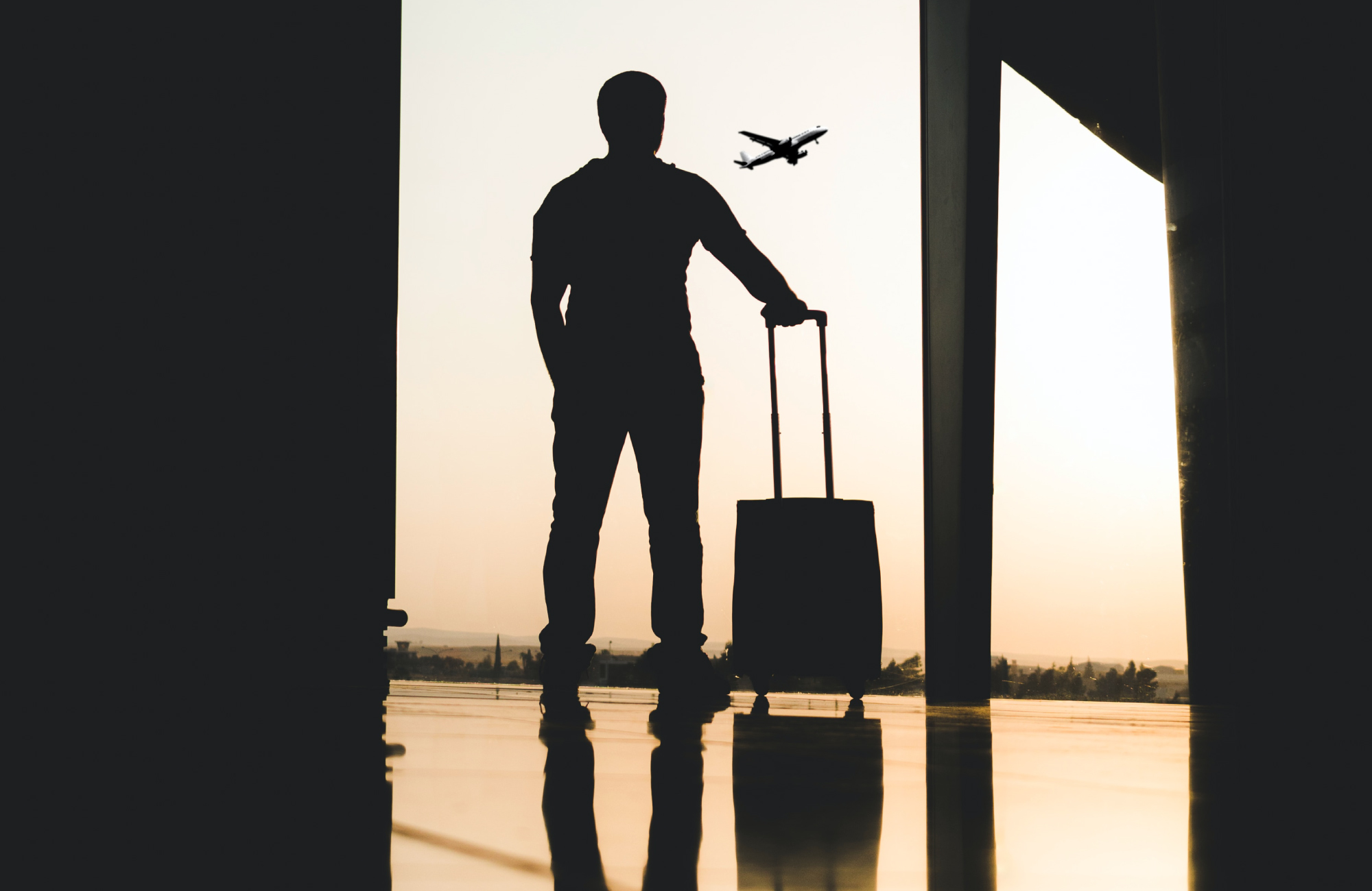 A traveller waits at an airport with their suitcase