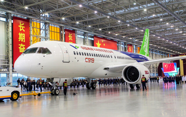 The Comac C919 aircraft in a hanger surrounded by people
